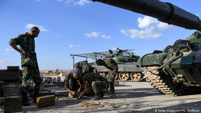 Members of the Syrian pro-regime forces prepare ammunition during the advance towards rebel-held positions west of Aleppo