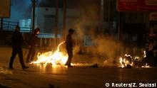 Riot police and protesters in a street with burning debris (Reuters/Z. Souissi)