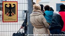 ARCHIV - Flüchtlinge stehen am 07.12.2015 neben einem Schild vom Bundesamt für Migration und Flüchtlinge an der Landesaufnahmebehörde Niedersachsen in Braunschweig (Niedersachsen). Das Thema Zuwanderung soll am 26. Oktober bei den Jamaika-Verhandlungen zur Sprache kommen. (zu dpa Zeitplan für Jamaika vom 25.10.2017) Foto: Julian Stratenschulte/dpa +++(c) dpa - Bildfunk+++ | Verwendung weltweit