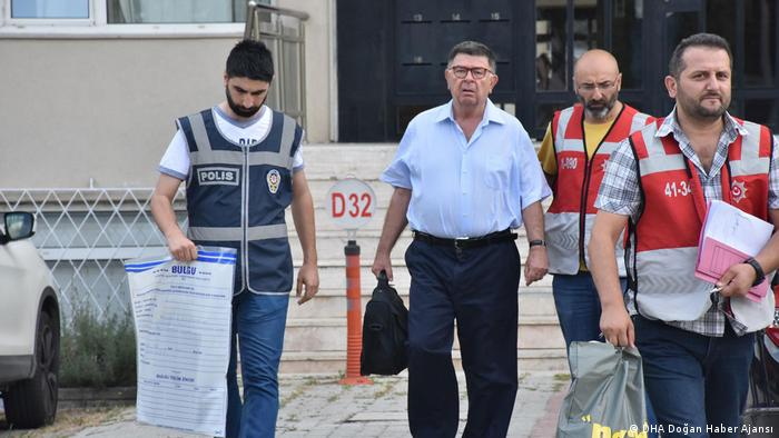 Sahin Alpay surrounded by police and health workers