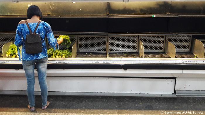 woman standing in front of near empty supermarket shelf
