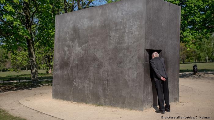 big grey cement block, man peeers into window