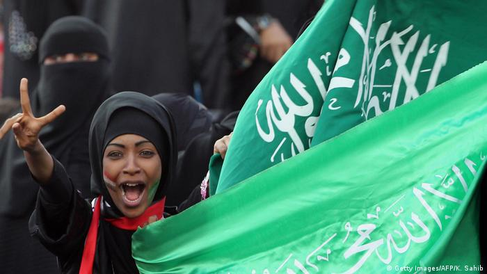Saudi woman holding up flag in stadium (Getty Images/AFP/K. Sahib)