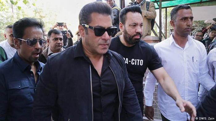 Salman Khan, wearing dark sunglasses, walks through a crowd of photographers.
