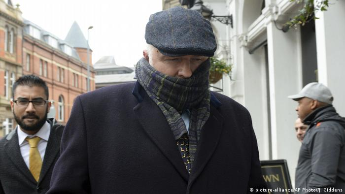 UK surgeon Simon Bramhall leaves court with a scarf covering the lower half of his face.