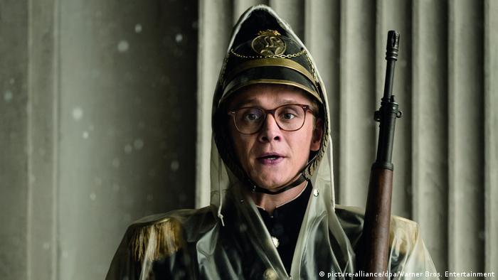 Filmstill von Hot Dog mit Matthias Schweighöfer in Uniform und Regencape mit Gewehr (picture-alliance/dpa/Warner Bros. Entertainment)