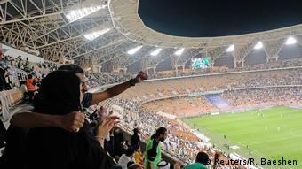 Woman hugged by a male family member at the Jiddah stadium