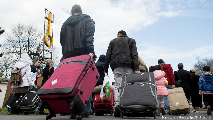 Syrian refugees pulling suitcases toward an asylum center in Germany