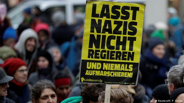 A protester carries a placard that reads: Lasst Nazis nicht Regieren (Don't let Nazis into government).