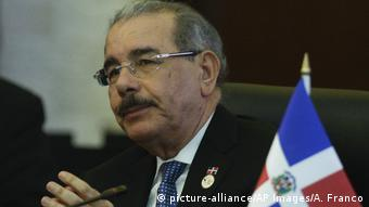 Danilo Medina listens next to a Dominican flag (picture-alliance/AP Images/A. Franco)