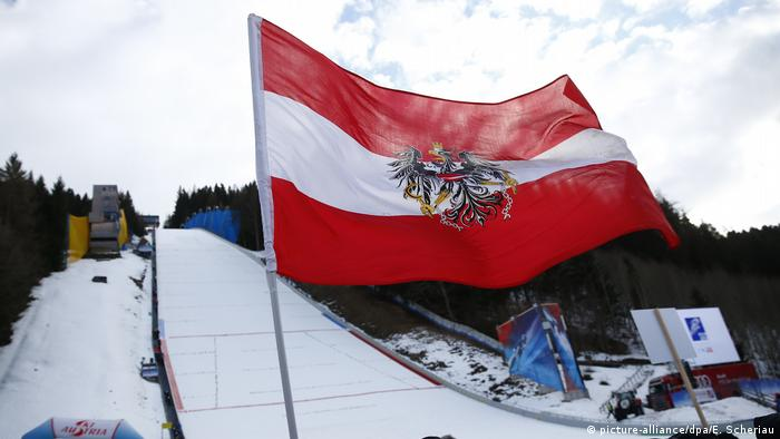 An Austrian flag flies in front of a ski jump (picture-alliance/dpa/E. Scheriau)