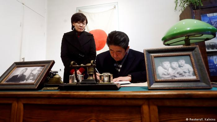 Japanese Prime Minister Shinzo Abe signs a guest book in the former home of Chiune Sugihara
