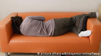 Mann schläft auf einer Couch (picture-alliance/Bildagentur-online/Tetra)
