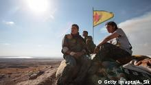 Kurdish People's Protection Units, or YPG fighters stand near a check point