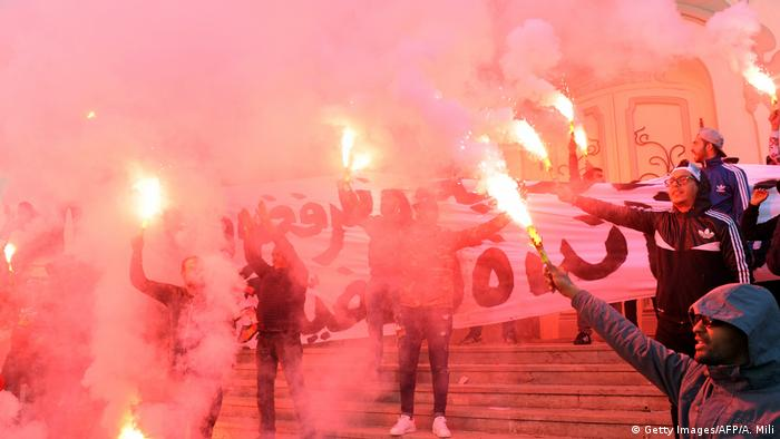 Tunisian protesters hold flares and shout slogans against the government