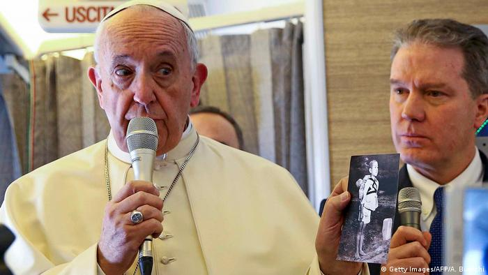 Pope Francis speaks into a microfone and holds a picture of a Nagasaki victim