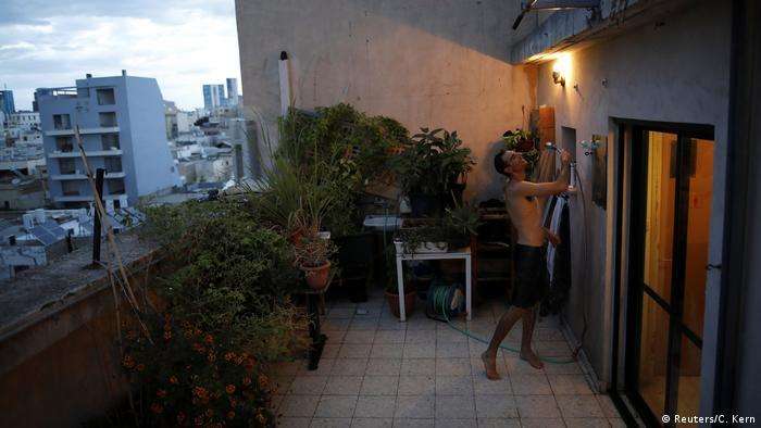 Молодой человек принимает душ на крыше