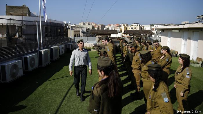 На крыше здания израильские солдаты с сержантом готовятся к параду