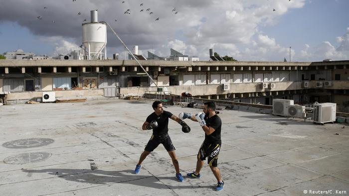 Двое мужчин отрабатывают на крыше навыки рукопашного боя крав-мага
