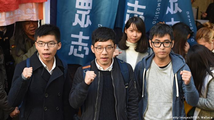 Joshua Wong, Nathan Law and Alex Chow hold up their fists outside the court of final appeal