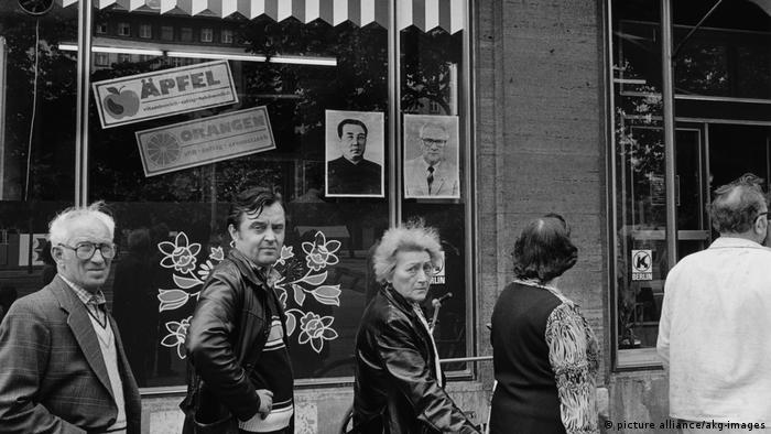 People queue outside a grocery in East Berlin in 1984. In the window, portraits of Kim Il-sung and Erich Honecker are posted side by side, marking Kim's first and last visit to East Germany.