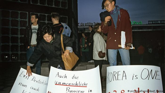 Koreans protest at the site of the Berlin Wall on November 10, 1989. They have banners with the messages: First Germany, now Korea too, KOREA is ONE, and the inhuman barriers in Korea must fall too. (picture-alliance/dpa/I. Bajzat)