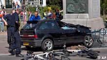 Police officers surround a car moments after it slammed into a monument in Apeldoorn, Netherlands, Thursday, April 30, 2009. Dutch television is reporting at least 14 people injured after a car careened into spectators watching Queen Beatrix's motorcade amid celebrations for the national holiday of Queen's Day. An Associated Press photographer who witnessed the incident said the car appeared to be deliberately driving at high speed toward an open bus carrying the queen and her family in the town of Apeldoorn. The car slammed into a monument. The royal bus was not hit and no one in the queen's entourage was injured. (AP Photo/Cynthia Boll)