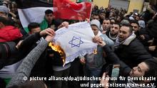 Demonstrators burn an Israeli flag (picture alliance/dpa/Jüdisches Forum für Demokratie und gegen Antisemitismus e.V.)