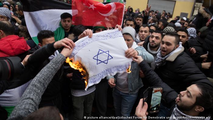 Demonstrators burn an Israeli flag