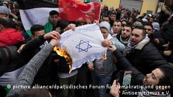 متظاهرون يحرقون علم عليه رسم نجمة داوود اليهودية (العلم الإسرائيلي) في حي نويكولن في برلين.