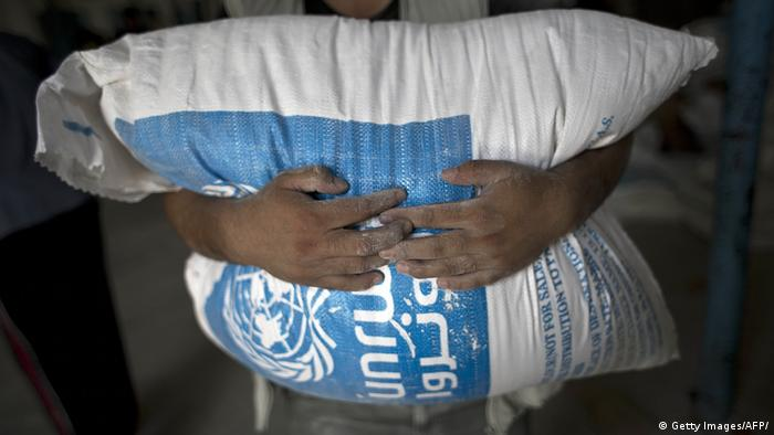 A man carries a bag of flour distributed at a UN aid distribution center (Getty Images/AFP/)