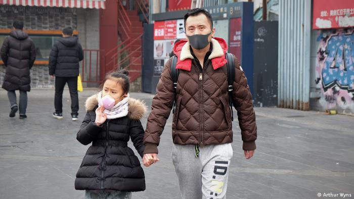 Homem com menina usando máscaras na China