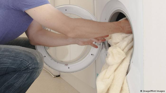 A man using the washing machine (Imago/Mint Images)