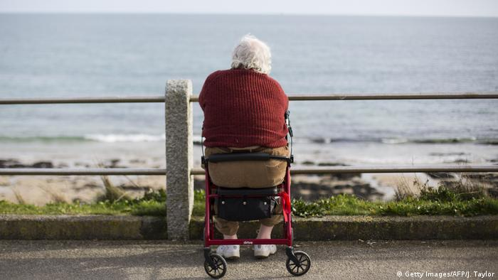 An elderly man looks out to sea