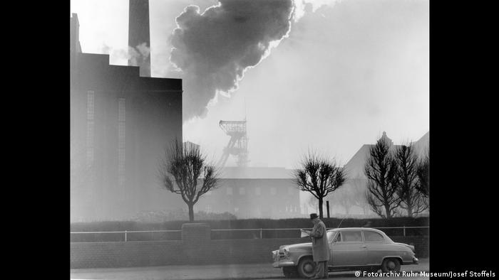 In black and white. Stoffels with his car in a smokey winter scene.(Photo Archive of teh Ruhr Museum)