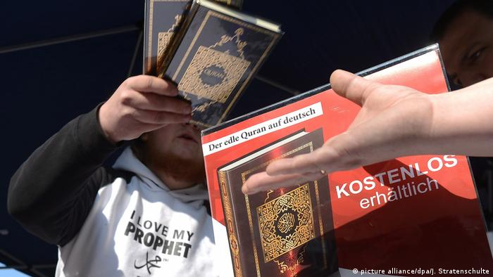 A man hands out free copies of the Koran while a hand reaches out for one