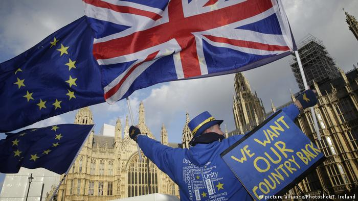 A demonstrator who wants Britain to remain in the European Union (EU) waves flags of the EU and Great Britain outside the Houses of Parliament in London