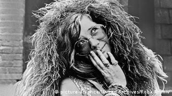 US-Sängerin Janis Joplin mit Wuschelfrisur, runder Brille und zahlreichen Armreifen und Ringen auf einem Schwarzweißbild