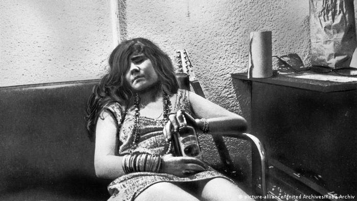 Janis Joplin, exhausted on a backstage couch and holding a bottle of Southern Comfort (picture-alliance/United Archives/Roba Archiv)