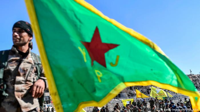 A member of the YPG and the group's flag