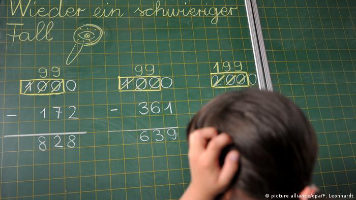 Symbolbild: Ein Mädchen steht vor einer Schultafel mit Rechenaufgaben und dem mit Kreide geschriebenen Satz: Wieder ein schwieriger Fall und hält sich den Kopf als Ausdruck 'Eigentlich habe ich keine Lust darauf'