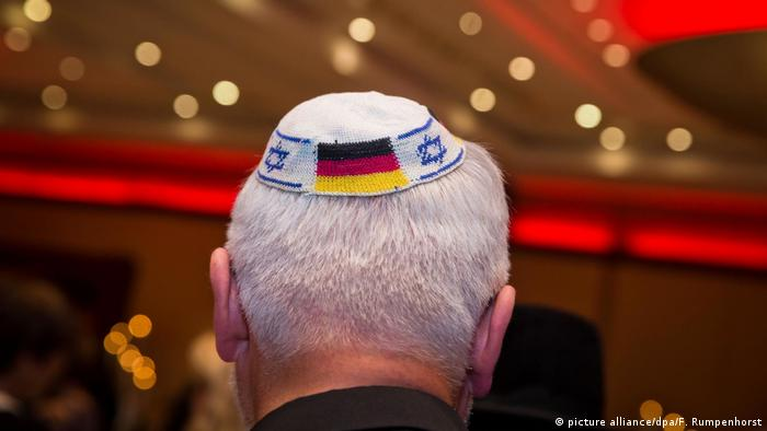 Jewish man wearing a kippah emblazoned with the German flag