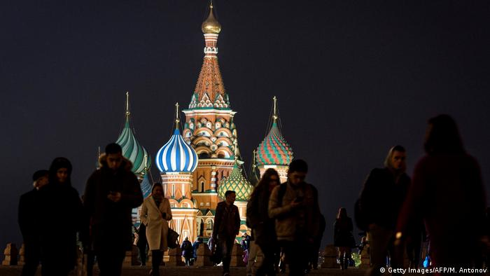 People walk in front of an illuminated St. Basil's Cathedral on Red Square in Moscow