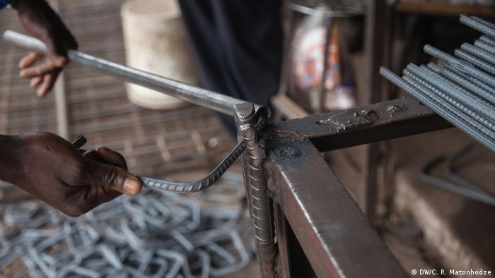 Photo shows a man bending steel with a vise at a workshop