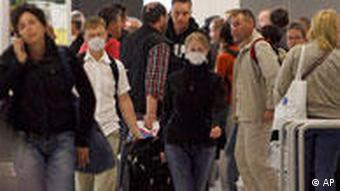 People wear masks to protect them from the swine flu at an airport