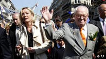 Le Pen walks with his daughter Marine as he waves to supporters