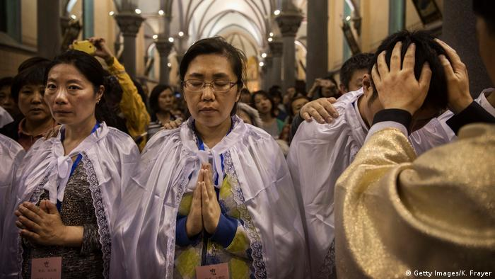 Chinese Catholic Bishop Zhang Hong blesses newly baptized worshippers at a mass on Holy Saturday in Beijing in 2017 (Getty Images/K. Frayer)