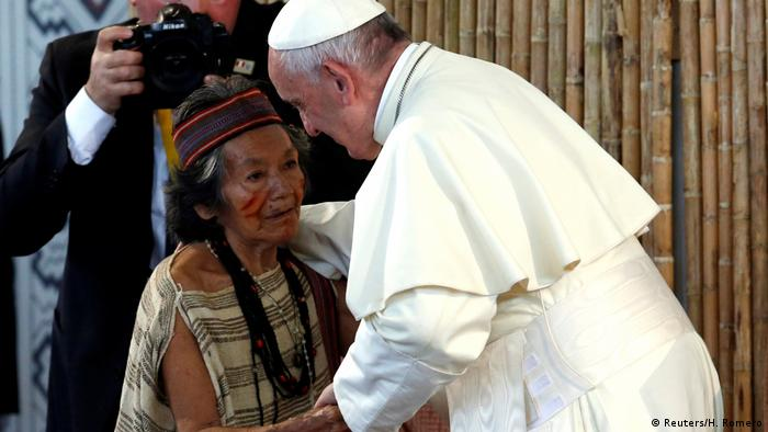 Pope Francis greets a member of a Peruvian indigenous group