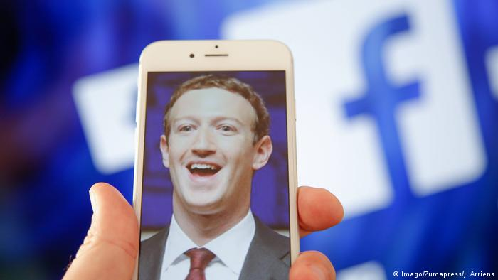 Mark Zuckerberg's face on a phone in front of a Facebook log