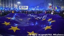 Demonstrators hold a giant flag of the European Union as they stage an anti-government and anti-corruption protest in front of the Romanian Parliament building in Bucharest January 20, 2018. More than 30,000 people in Bucharest and in other cities across the country demonstrated against the policy of the ruling social democratic PSD party and a new legislation that has sparked concerns in Brussels and Washington about the shaky government's commitment to fighting endemic corruption. / AFP PHOTO / Daniel MIHAILESCU (Photo credit should read DANIEL MIHAILESCU/AFP/Getty Images)